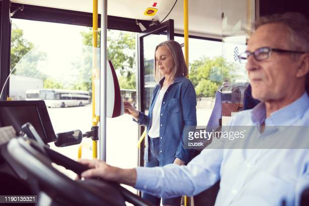 woman paying fare through contactless payment - fare stock pictures, royalty-free photos & images