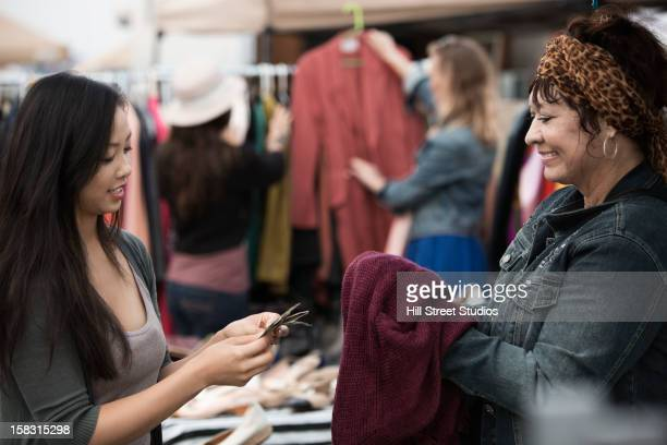 Woman paying for clothing at flea market