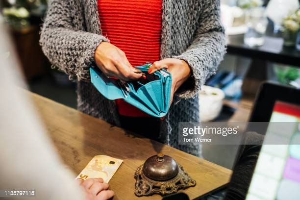 woman paying for flowers at florist - black purse stock pictures, royalty-free photos & images
