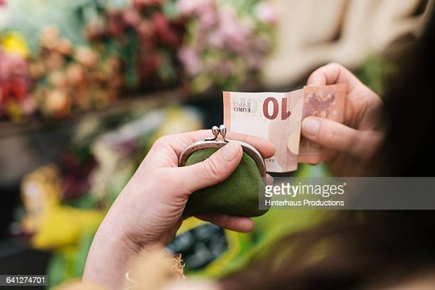 Woman paying for Flowers with 10 Euro Bill