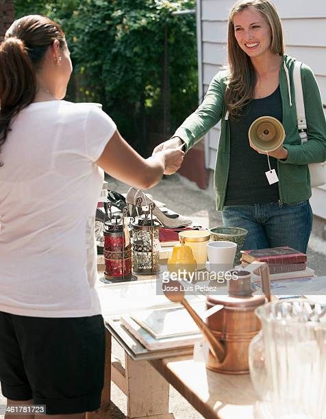 woman paying for item at garage sale - venta de garaje fotografías e imágenes de stock