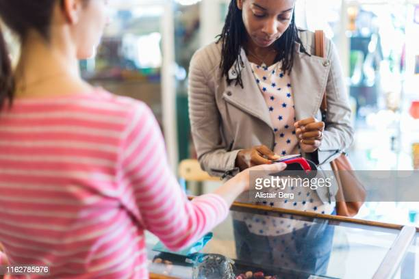 woman paying for jewelry with contactless payment technology in a clothes store - financial technology stock pictures, royalty-free photos & images