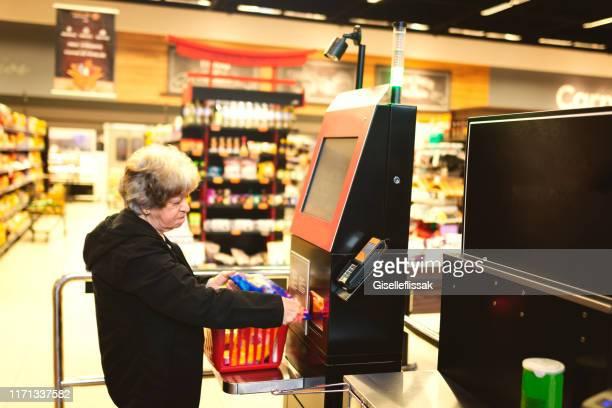 セルフサービスでスーパーマーケットで支払う女性 - セルフサービス ストックフォトと画像