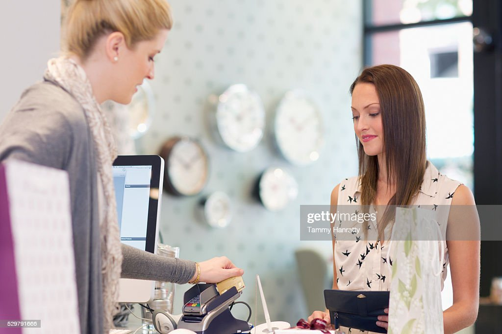 Woman paying in clothing store : Stockfoto
