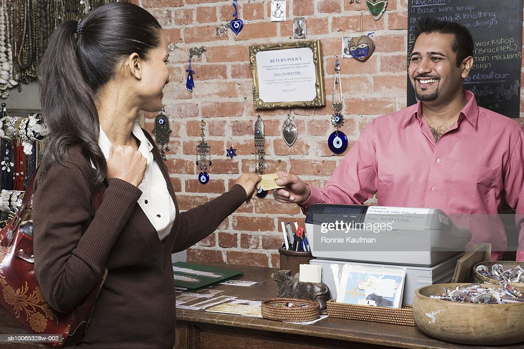 Woman paying man with credit card in shop : Foto stock