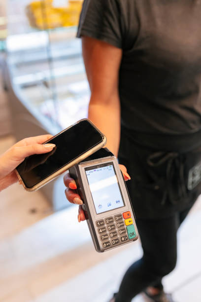 Woman paying online through mobile phone to waitress at food court