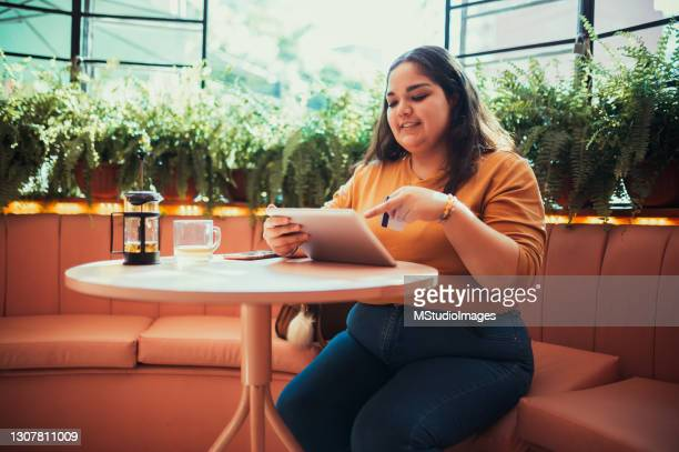 woman paying online with her credit card - three quarter length stock pictures, royalty-free photos & images