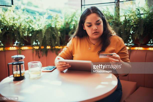 woman paying online with her credit card - chubby credit stock pictures, royalty-free photos & images