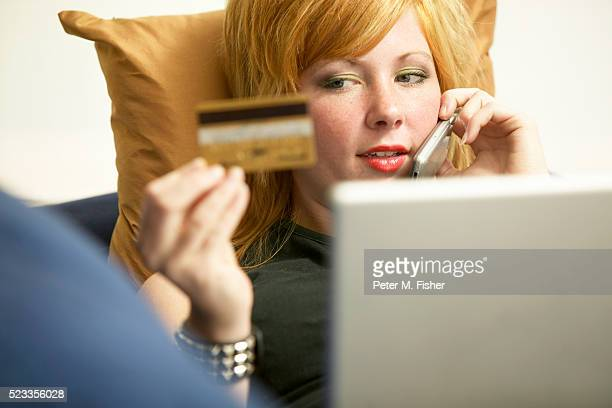 woman paying over the phone with credit card - identity theft stock pictures, royalty-free photos & images