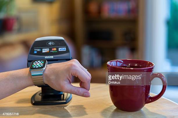 woman paying using apple watch and electronic reader - nfc stock pictures, royalty-free photos & images
