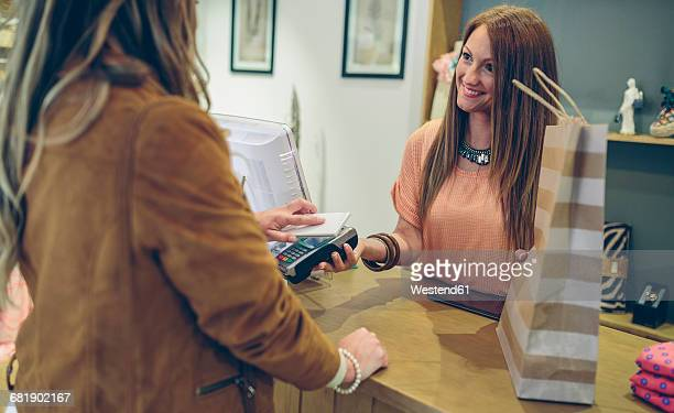 Woman paying using smartphone with NFC technology in a store