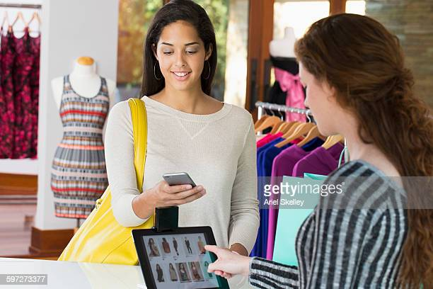 Woman paying with cell phone in store