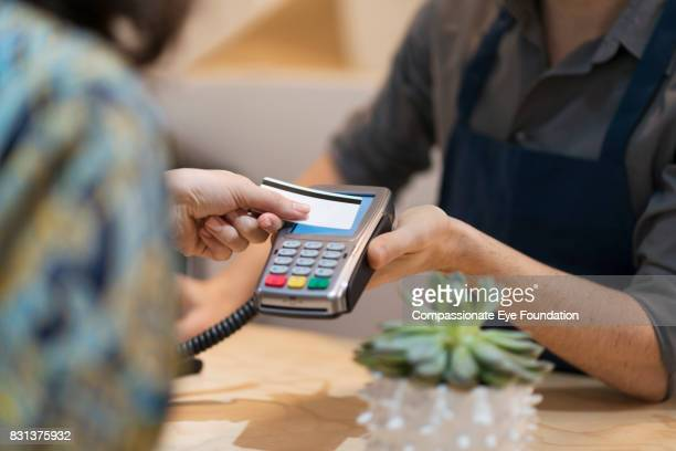 Woman paying with contactless credit card in flower shop