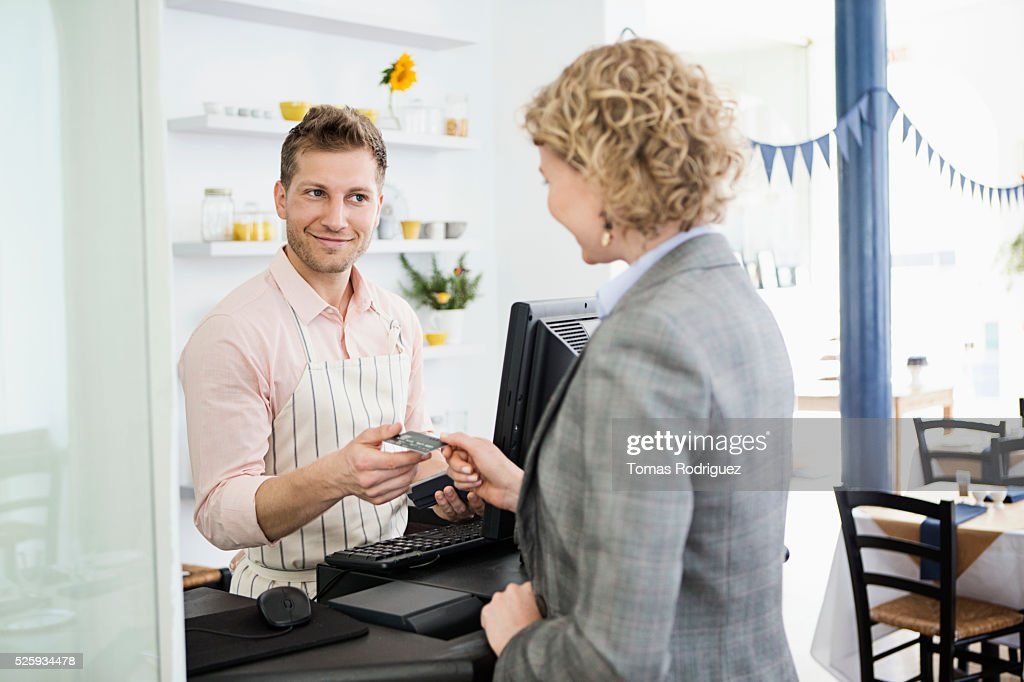 Woman paying with credit card at checkout counter in cafe : Stock Photo