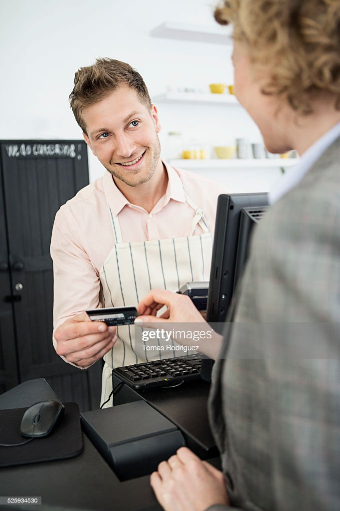 Woman paying with credit card at checkout counter : Stock Photo