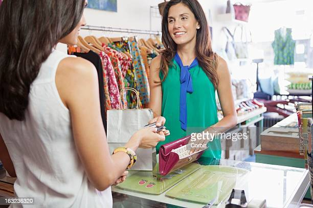 Woman paying with credit card in clothes store
