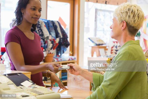 Woman paying with credit card in fabric store