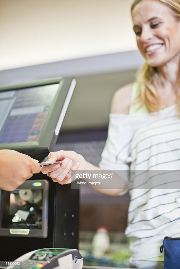 Woman paying with credit card in store : Stock Photo