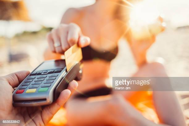 Woman paying with credt card on the beach
