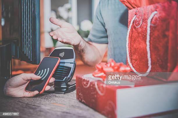 Frau bezahlen mit NFC-Technologie auf Smart Phone in Store