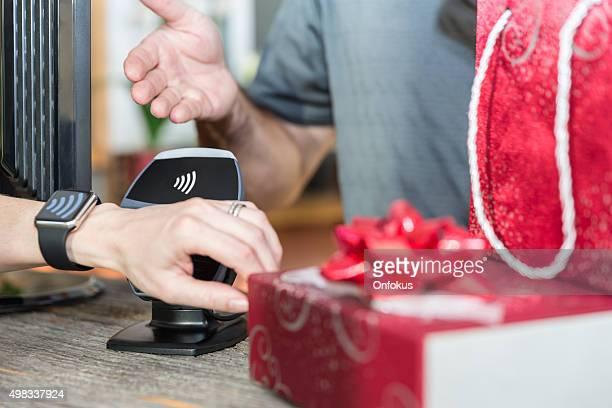 Frau bezahlen mit NFC-Technologie auf Smart Watch im Store