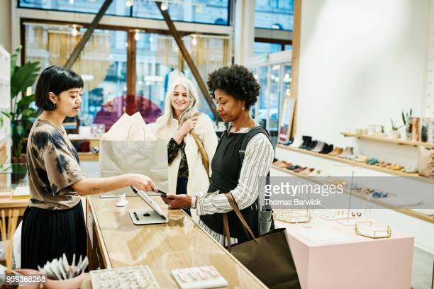 woman paying with smartphone after shopping in boutique with friend - older women in short skirts stock pictures, royalty-free photos & images