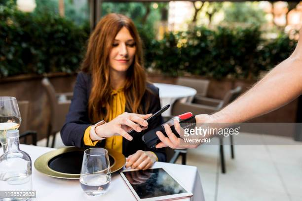woman paying with smartphone in a restaurant - paying stock pictures, royalty-free photos & images