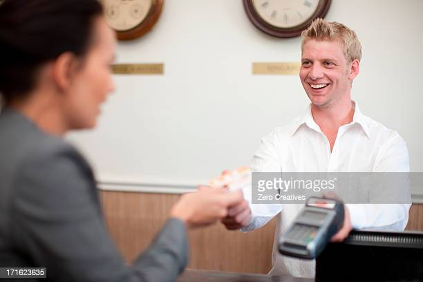 Woman paying young man on hotel reception