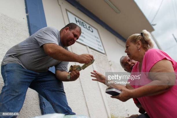 A woman pays a vendor for a bag of ice at a local plant in the aftermath of Hurricane Maria in Arecibo Puerto Rico September 30 2017 US military and...