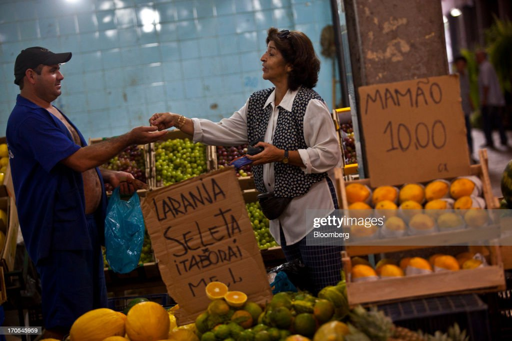 A woman pays for purchases at a market in Rio de Janeiro, Brazil, on Thursday, June 13, 2013. Brazilian retail sales rose in April at less than half the pace economists forecast as inflation erodes purchasing power, complicating the governments effort to boost growth. Photographer: Dado Galdieri/Bloomberg via Getty Images