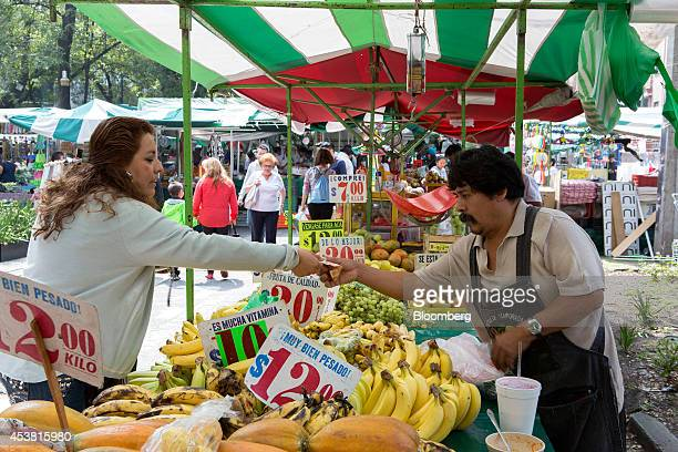 A woman pays for some fruit at an outdoor market in the La Condesa neighborhood of Mexico City Mexico on Friday Aug 15 2014 Mexicans can spend less...