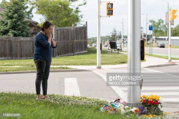 Woman pays her respects at the scene where a man driving a pickup truck struck and killed four members of a Muslim family in London, Ontario, Canada...