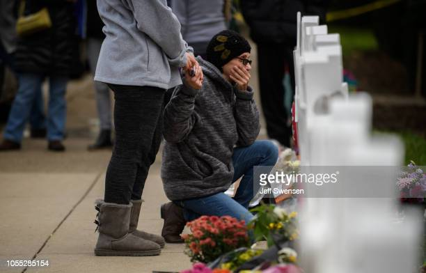 A woman pays her respects in front of at a memorial for victims of the mass shooting that killed 11 people and wounded 6 at the Tree Of Life...