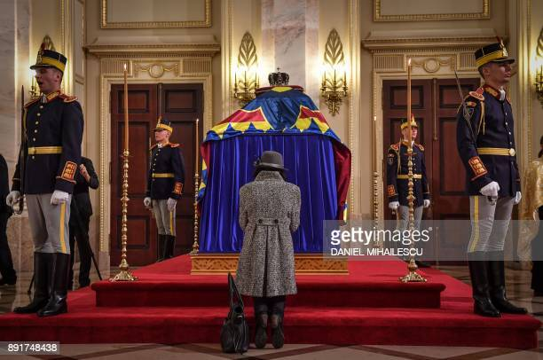 A woman pays her respects in front of the coffin of King Michael I of Romania on December 13 2017 at the former Royal Palace that houses the National...
