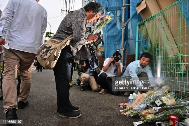 A woman pays her respects next to flower tributes at the crime scene where a man stabbed 19 people including children in Kawasaki on May 28 2019 A...