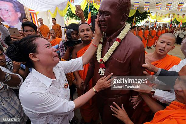A woman pays her respects to prominent political analyst Kem Ley just in front of his statue during a funeral ceremony to mark 100 days since his...
