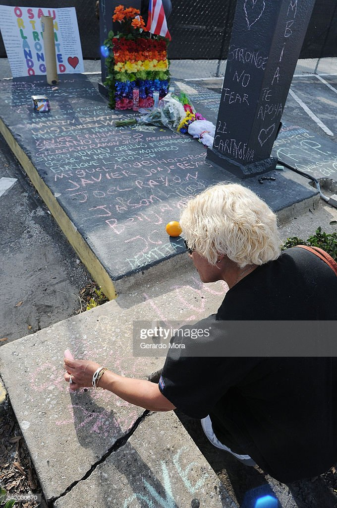 A woman pays her respects to the victims of the Pulse nightclub shooting at the front of the nightclub building on June 21, 2016 in Orlando, Florida. The Orlando community continues to mourn the victims of the deadly mass shooting at a gay nightclub.