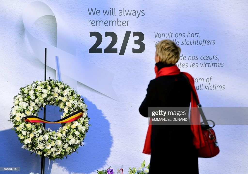 A woman pays her respects to victims in front of a wall and a wreath laid out for victims at Brussels' international airport in Zaventem during a memorial ceremony to mark the first anniversary of the twin Brussels attacks by Islamic extremists on March 22, 2017. Belgium marks the first anniversary of the Islamic State bombings in Brussels, one at the airport and the other in the metro, in which 32 people were killed and more than 320 wounded with ceremonies showing that the heart of Europe stands defiant. / AFP PHOTO / Emmanuel DUNAND