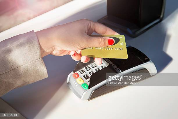 Woman pays with creditcard contactless on reader.