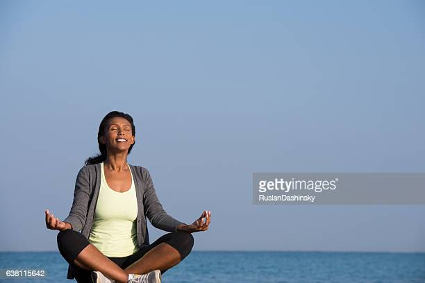 Woman peaceful meditation on seashore.