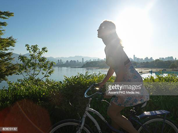Woman pedaling cruiser bike past city and pool