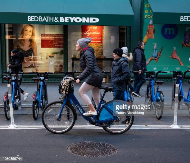 Woman pedals past a BedBath & Beyond store on a rented Citi Bike bicycle in New York City on December 7, 2018. The Citigroup is the main sponsor of...