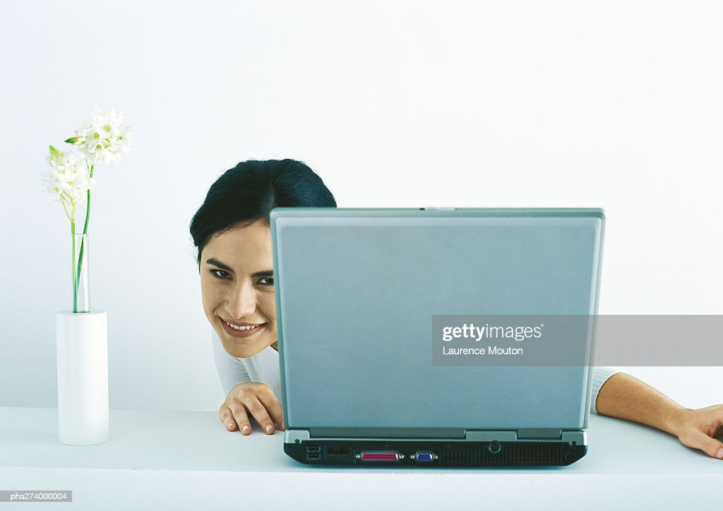 Woman peeking around side of laptop : Stockfoto