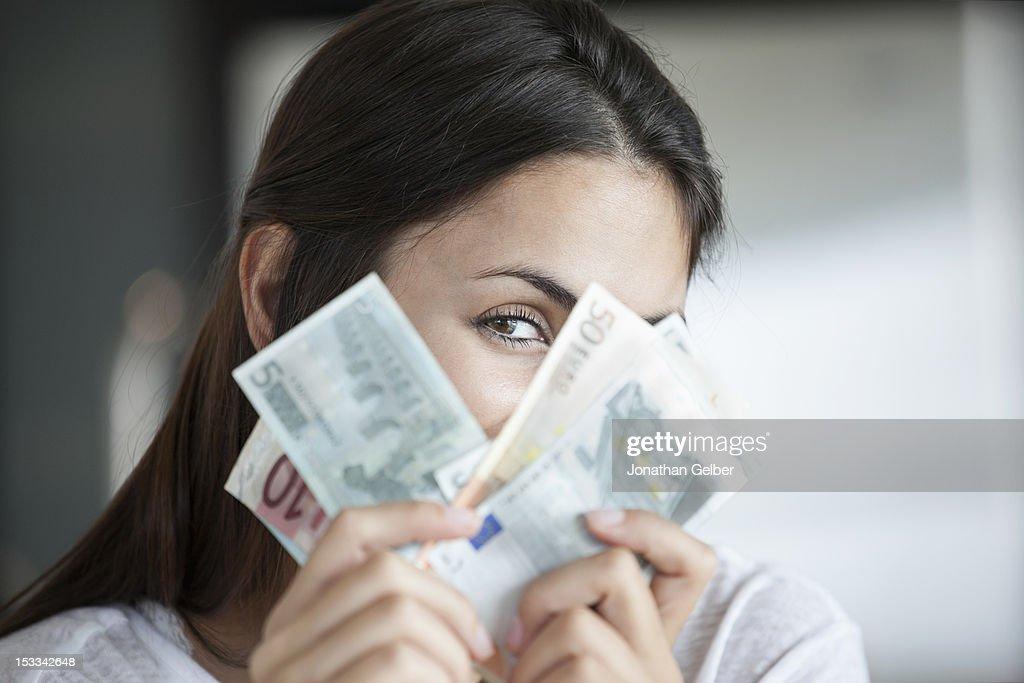 Woman peeking behind euro notes : Stock Photo