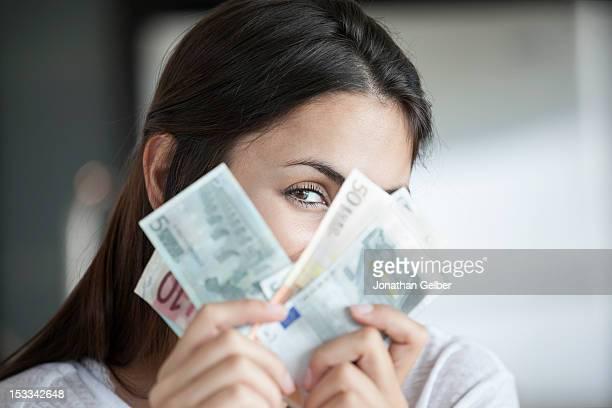 woman peeking behind euro notes - geld verdienen stock-fotos und bilder
