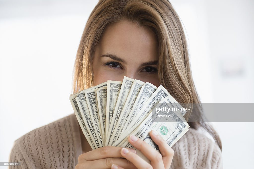 Woman peeking behind money : Stock Photo
