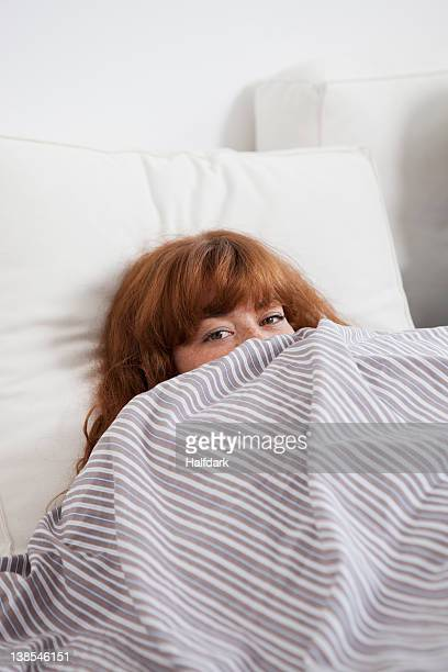 A woman peeking from behind a duvet in bed