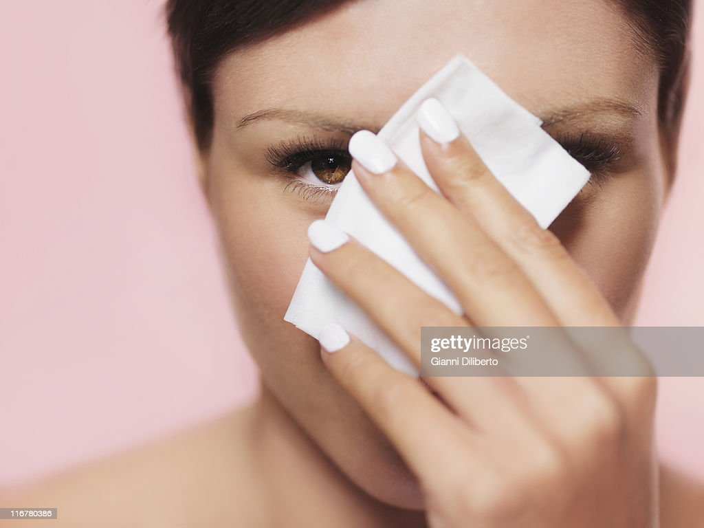 A woman peeking from behind a tissue : Stock Photo