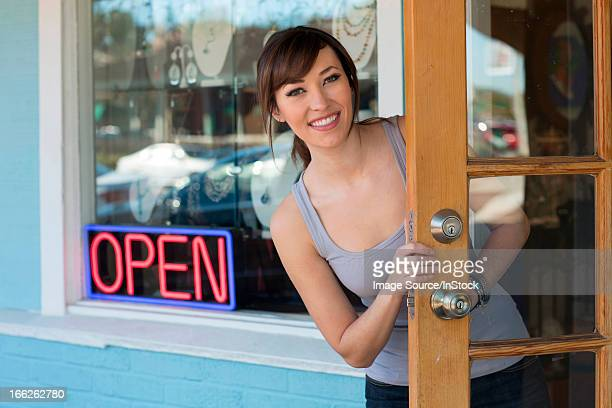 Woman peeking out front door of store
