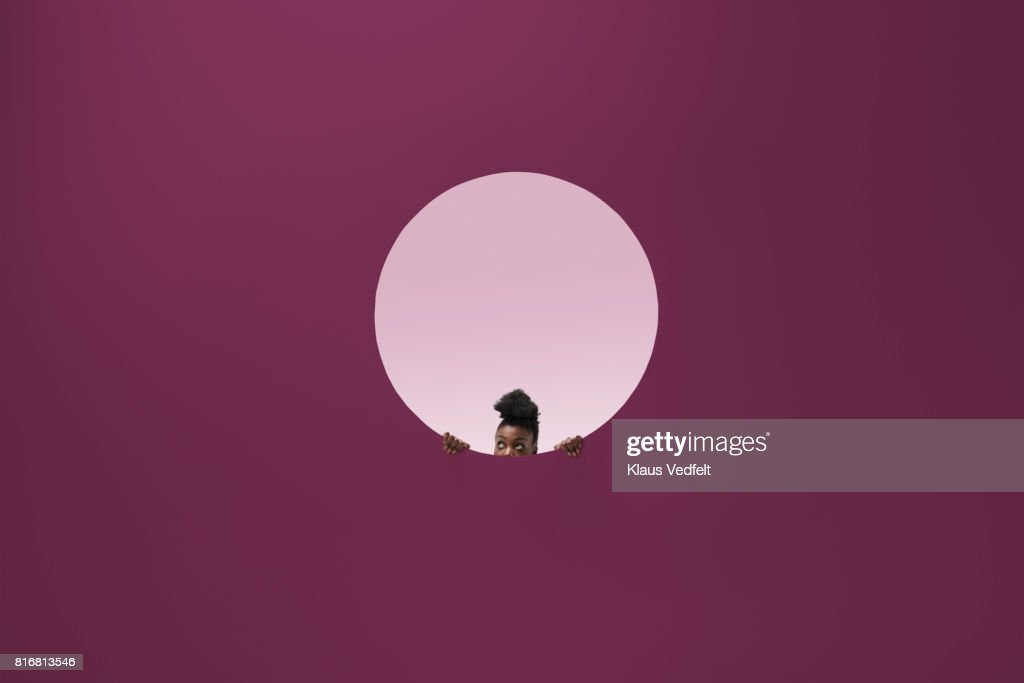 Woman peeking out of round opening in coloured wall : Stock Photo
